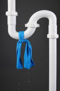 plumbing pipe with blue cloth tied around it
