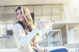 Woman drinking a glass of water. She is sitting on the terrace outside her luxury home. Kitchen in the background. She is smiling. Copy space